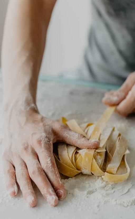 Hände kneten Nudelteig auf bemehlter Arbeitsfläche