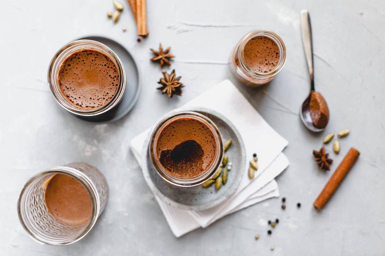 Schokomousse mit Lebkuchengewürz in Gläschen serviert und Sternanis sowie Cardamomkapseln und Zimtstangen dekoriert