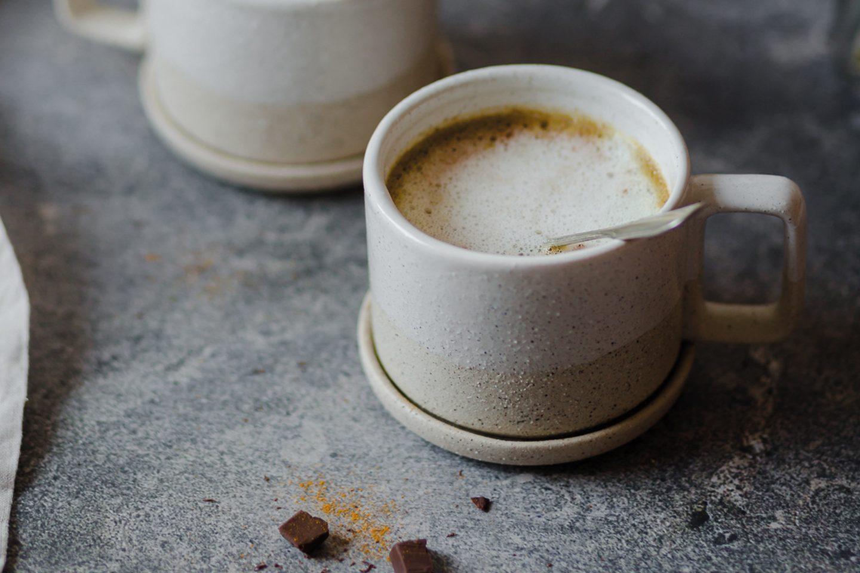 Tasse mit heißer Curcuma-Schokolade und etwas Schokolade auf grauem Untergrund