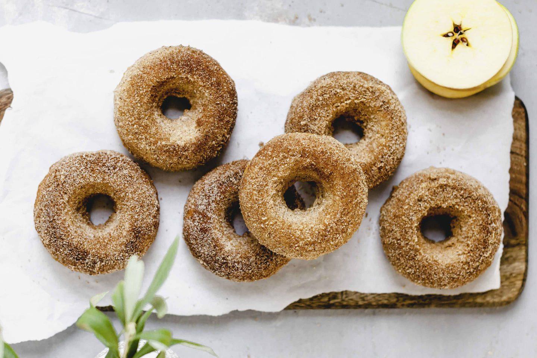 Apfelstrudel-Donuts in Zimt-Zucker gewendet und auf einem Stück Backpapier angerichtet
