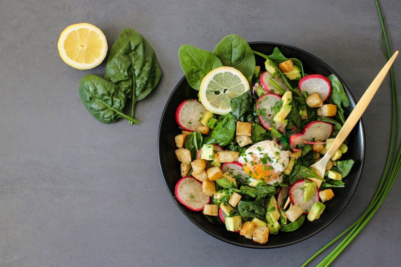 Salat-Bowl mit Spinat und Kräuter Rustikana gewürzt in einer schwarzen Schale mit einem Holzlöffel
