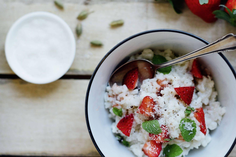 Kokosmilchreis mit Cardamom und Erdbeeren in einer weißen Schüssel mit blauem Rand