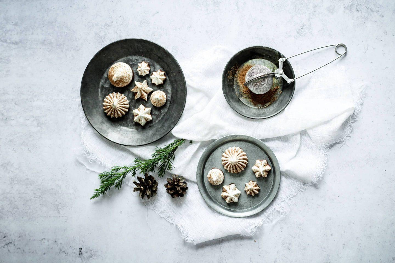 Chai-Baiserküsschen auf hellgrauen Tellern mit Weihnachtsdekoration