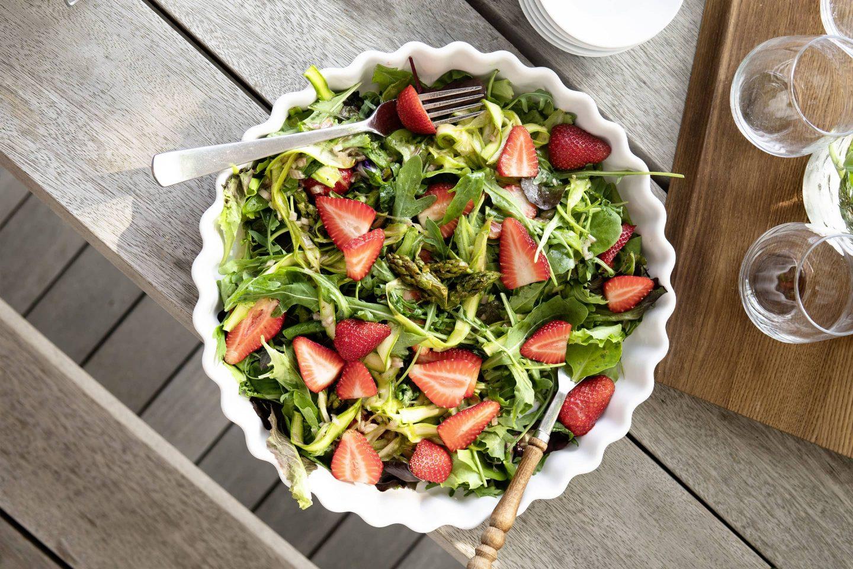 Erdbeer-Spargel-Salat mit Grillgewürzsalz in einer großen weißen Schüssel angerichtet und auf einem Holztische stehend.