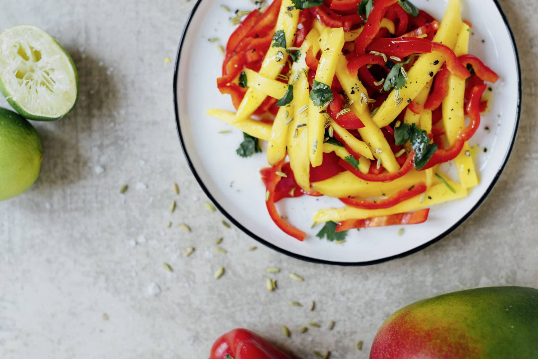 Mango-Fenchel-Salat auf einem weißen Teller mit blauem Rand, daneben eine Mango und halbierte Limetten