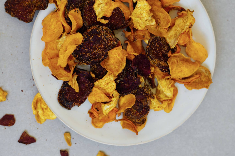 Gemüsechips mit Curry und Cayennpfeffer auf einem weißen flachen Teller
