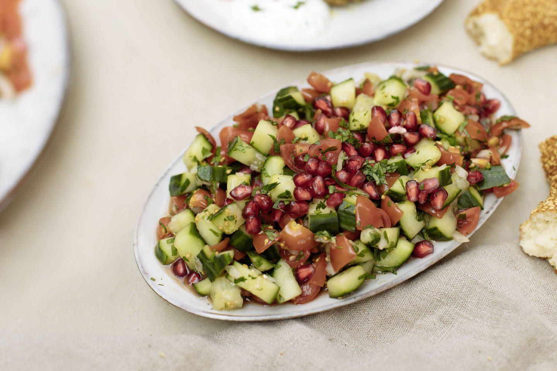 Grillgewürz-Köfte mit Ezme Salat und einem halben Sesamring auf einer Leinentischdecke