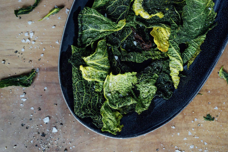 Grünkohlchips mit Curcuma in einer schwarzen, ovalen Schale