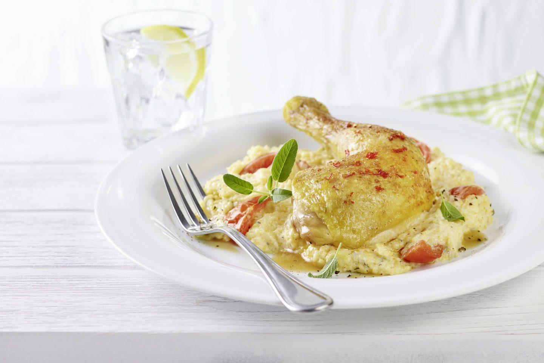 Hühnerkeule mit Polenta und Knoblauch auf einem weißen Teller mit einer Gabel