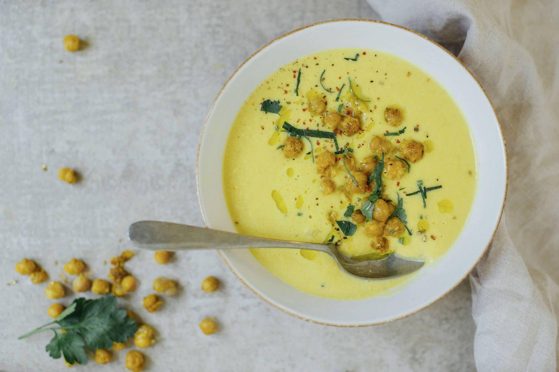 Kichererbsen-Suppe mit Curcuma, Koriander und Ingwer in einer weißen Schale mit Löffel