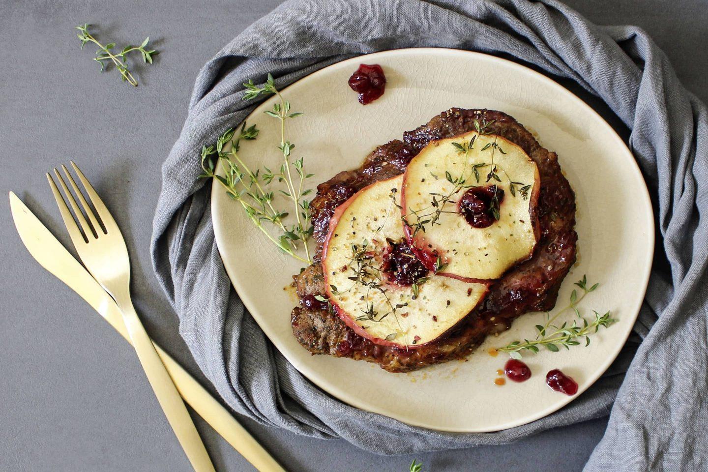 Kotelett mit Apfelscheiben und Preiselbeeren garniert auf einem hellen Teller mit grauer Serviette und goldenem BEsteck