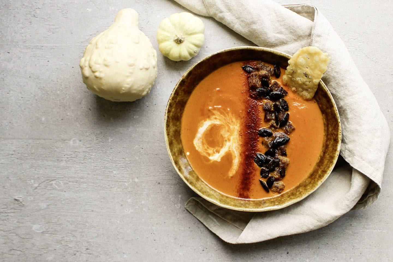 Kürbissuppe mit geriebener Muskatnuss und gerösteten Kürbiskernen in einem tiefen Teller angerichtet; daneben liegen Zierkürbisse und eine beige Serviette