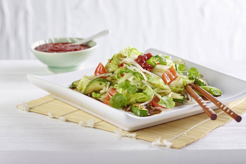 Lauwarmer Asiasalat mit gemahlenem Ingwer auf einem quadratischen Teller mit Essstäbchen