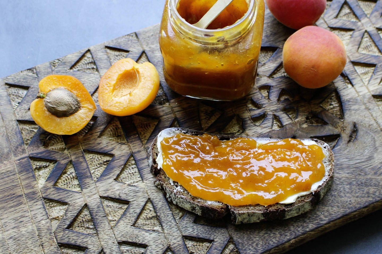 Marillenmarmelade mit Veggy Sweet in einem Marmeladenglas mit einem Brot und frischen Marillen auf einem Holzbrett