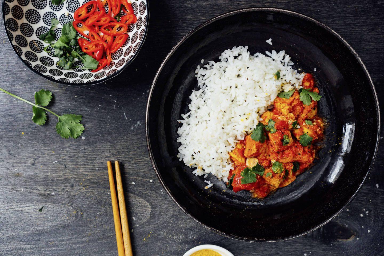 Neapesisches-Cardamom-Huhn mit Reis auf einem tiefen weißen Teller mit Essstäbchen und einer schwarz-weiß-gemusterten Schale mit fein geschnittener frischer Chili