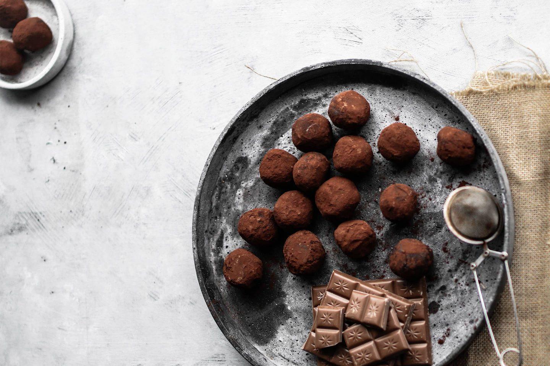 Orangenschokolade-Trüffel Pralinen mit Bourbon Vanille und in dunklem Kakaopukver gewälzt auf einem grauen Teller