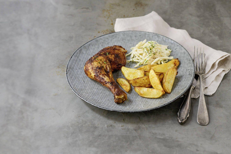 Kartoffelspalten mit Paprika gewürzten Hühnerkeulen.