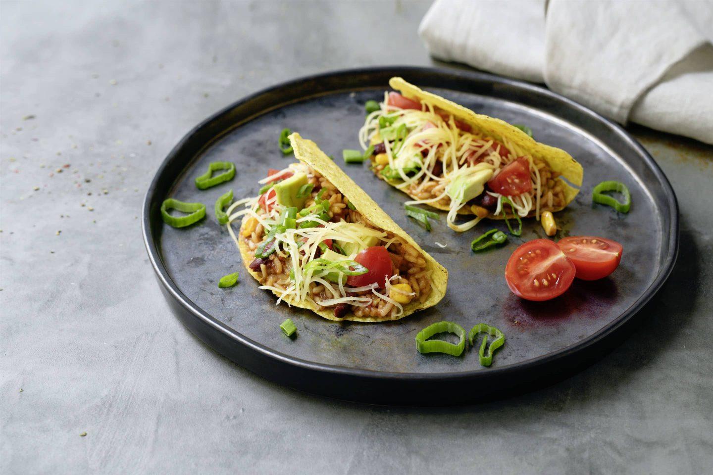 2 Stück Vegetarische Tacos mit Salsa und Reis gefüllt auf einem schwarzen Teller