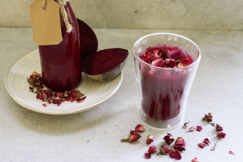 Rote Rüben Smoothie mit gemahlenem Ingwer in einem Glas mit Rosenblüten garniert
