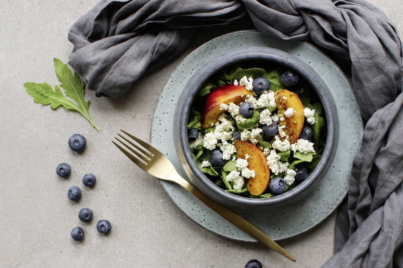 Salat mit zerbröseltem Ziegenkaese, frischen Blaubeeren und Pfirsich in einer hellblauen Schale
