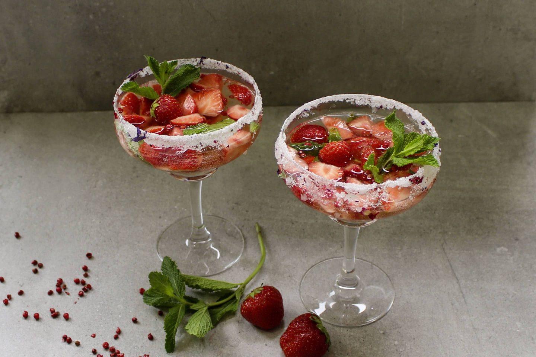 Sommer Bowle mit Rosa Beere und frischen Erdbeerstücken in gezuckerten Cocktailgläsern mit frischer Minze garniert