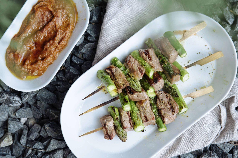 Steak-Gewürzsalz-Spieße mit Spargel auf einem weißen länglichen Teller und Ajvar dazu in einem separaten Schälchen