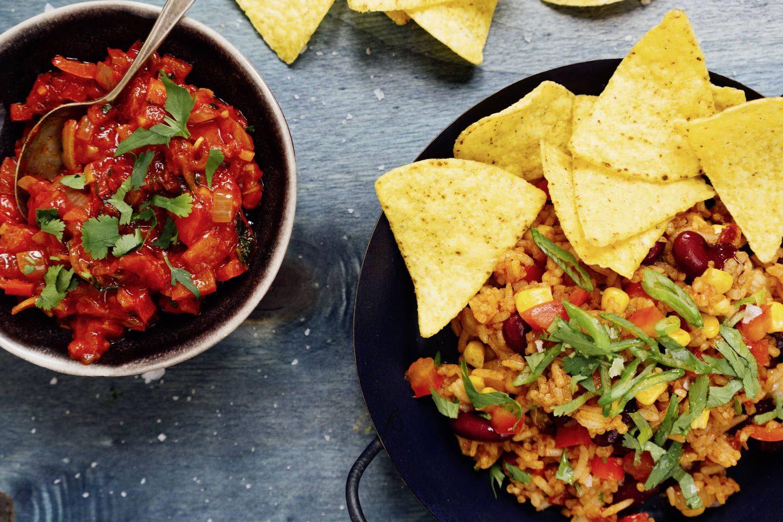 Tacoreis mit Cumin und Salsa in einer schwarzen kleinen Pfanne mit Tortilla-Chips angerichtet
