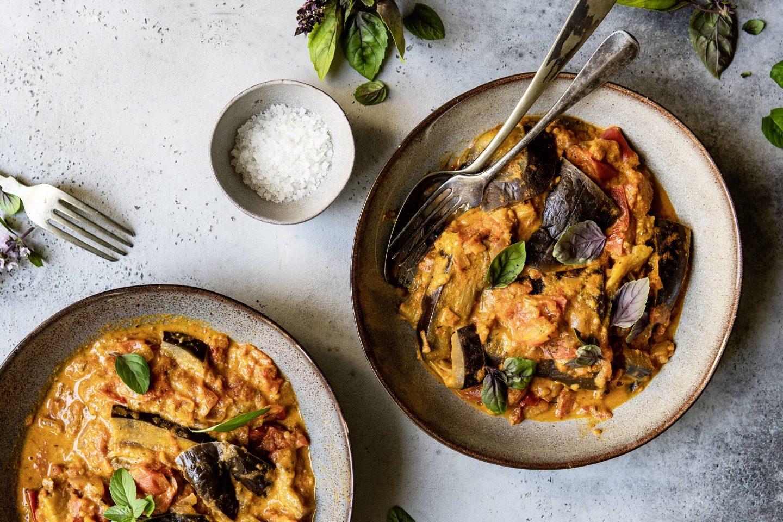 Tahin-Melanzani-Eintopf mit Veggy Classic Gewürzmischung auf 2 tiefen Tellern angerichtet und mit frischem Basilikum garniert