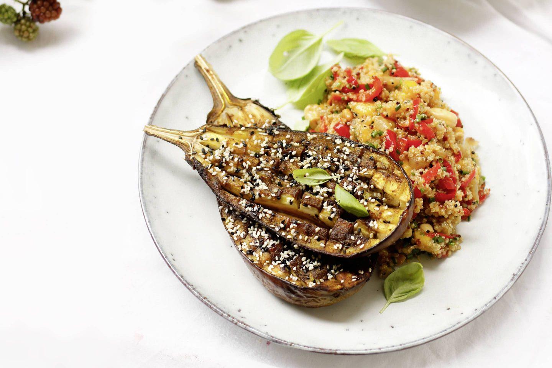 Gebackene Melanzani mit Quinoa-Mango-Salat auf einem weißen Teller mit frischen Basilikumblättern