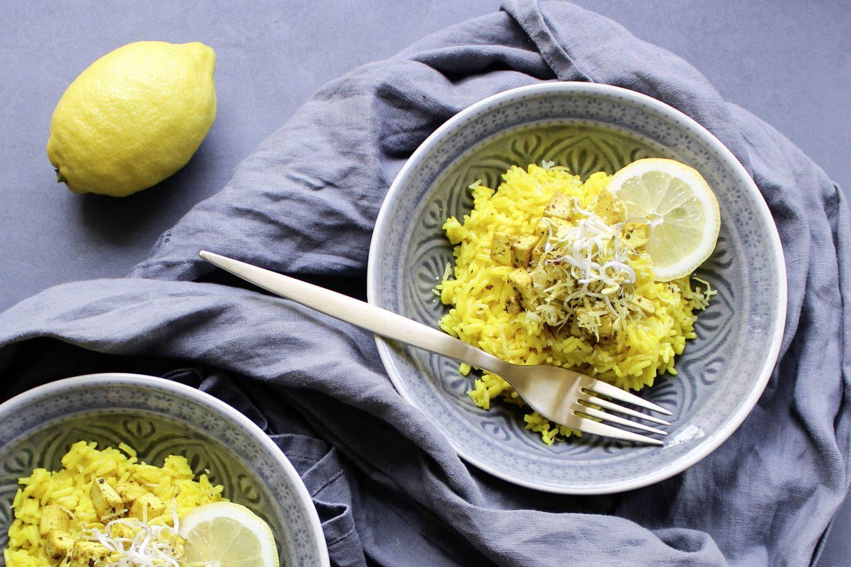 Zitronenreis mit Tofu und Veggy Exotic in gemusterten Schalen mit einer Gabel und mit Zitronenscheiben garniert