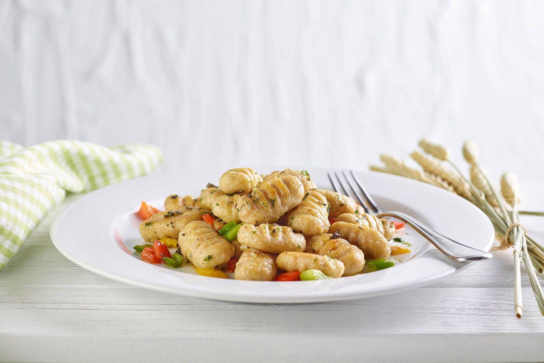 Vollkorn Gnocchi mit frischem Salbei und Paprika auf einem weißen Teller