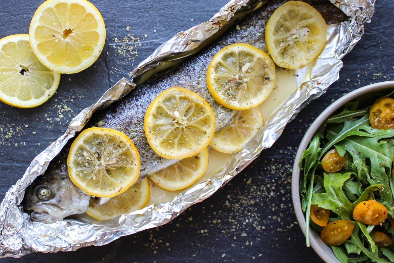 eine ganze Forelle mit Zitronenscheiben belegt in Alufolie und einer Schüssel mit Rucola-Tomaten-Salat