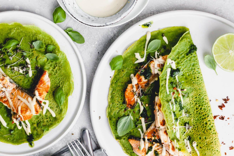 Grüner Basilikum-Lachs-Crepe mit frischem Basilikum verziert auf weißen Tellern