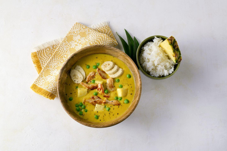 Ananas-Bananen-Hühner Eintopf mit Curcuma & more und Reis in einer braunen Schüssel und mit einer gelben Stofferviette angerichtet