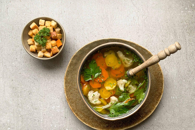 Gemüsesuppe mit Knoblauchcroutons in einer rustikalen Schale mit Holzlöffel serviert