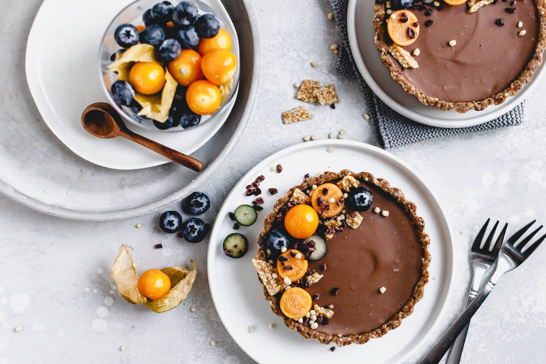 Schoko Tartelettes mit frischen Physalis und Blaubeeren dekoriert und auf Tellern angerichtet
