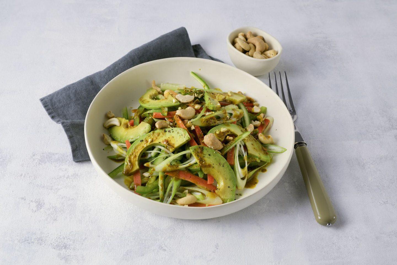 Asia-Salat mit gebratener Avocado und Cashewkernen in einer cremefarbenen Schale