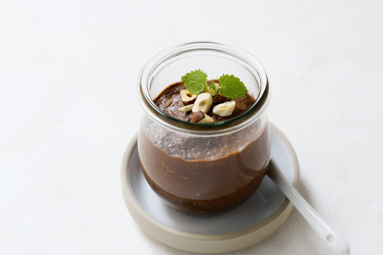Avocado-Vanille Schokomousse mit Haselnuss und frischer Minze garniert und in einem Gläschen mit Löffel angerichtet