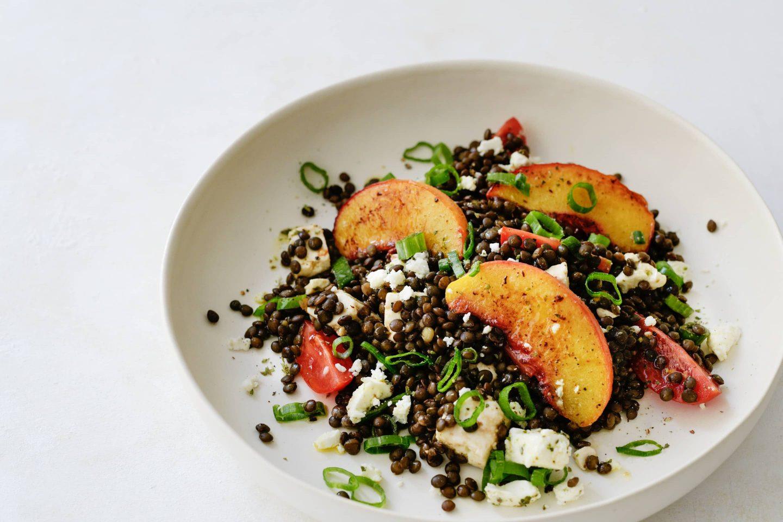Belugalinsensalat mit Pfirsich und Feta und Bio-Majoran gewürzt in einem hellen tiefen Teller