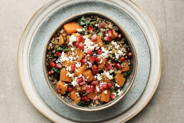 Quinoa-Winter-Bowl mit Kürbis und Granatapfelkernen in einer Schüssel