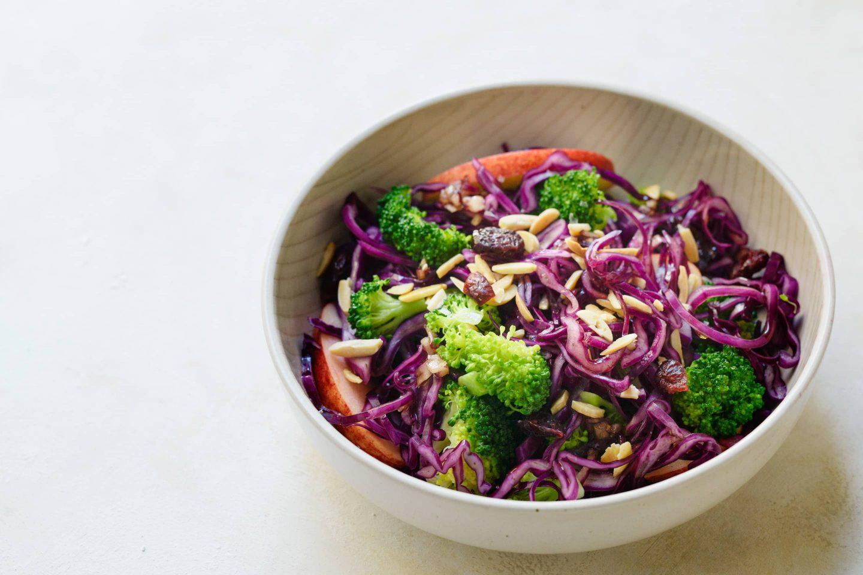 Winterlicher Brokkoli-Rotkraut Salat mit Rosmarin, Äpfeln und Mandeln in einer cremefarbenen Schüssel