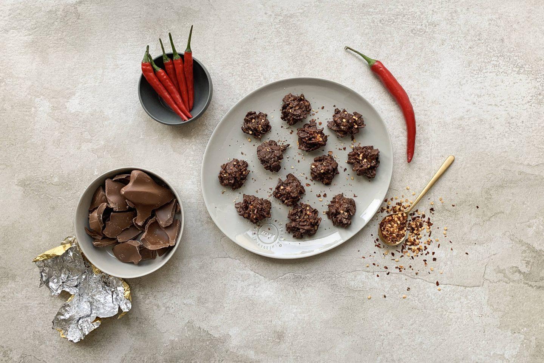 Schoko Crispies mit Meersalz und Chili auf einem grauen Teller mit Chilischoten und etwas Schokolade angerichtet