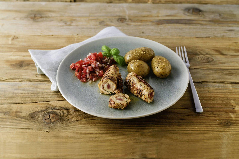 Grill-Gefluegel Involtini mit Kartoffeln und Tomatensalsa auf einem hellgrauen Teller