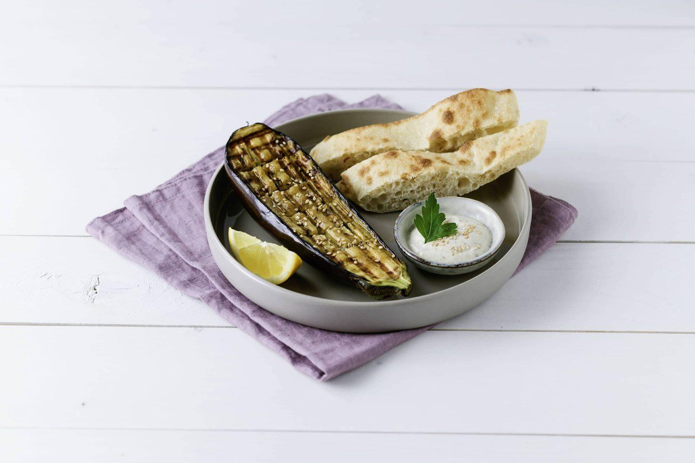 gegrillte Melanzani mit Pita und Sesam-Dip auf einem grauen Teller mit lilafarbener Serviette