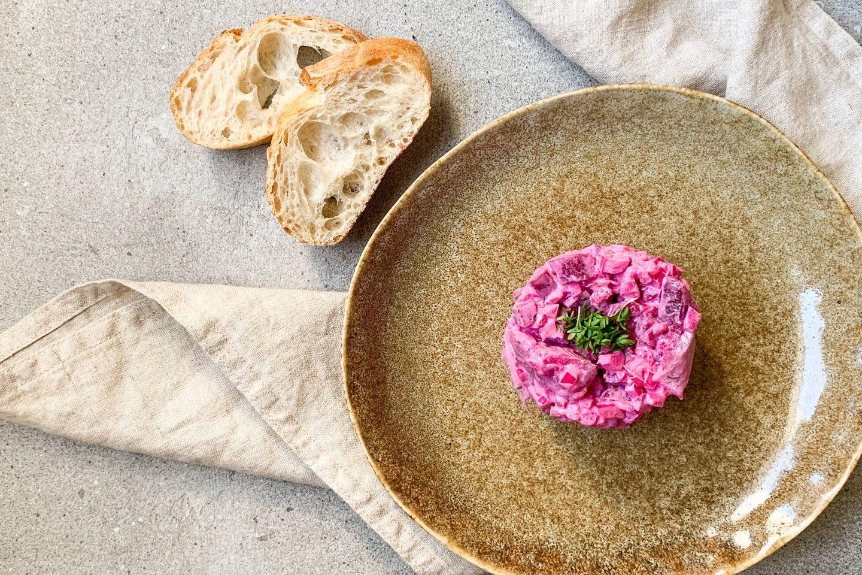 Heringsalat mit Roten Rüben auf einem rustikalen, ockerfarbenen Teller mit 2 Stück Baguette