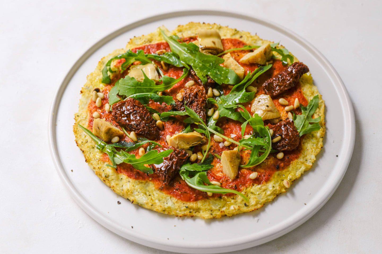 Karfiolpizza Karfiolpizza mit Rucola, getrockneten Tomaten und Artischocken auf einem weißen Teller