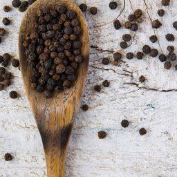 schwarzer Pfeffer auf einem Holzlöffel
