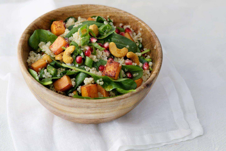 Quinoa-Spinat-Salat mit Süßkartoffeln und Granatapfelkernen in einer Holzschüssel