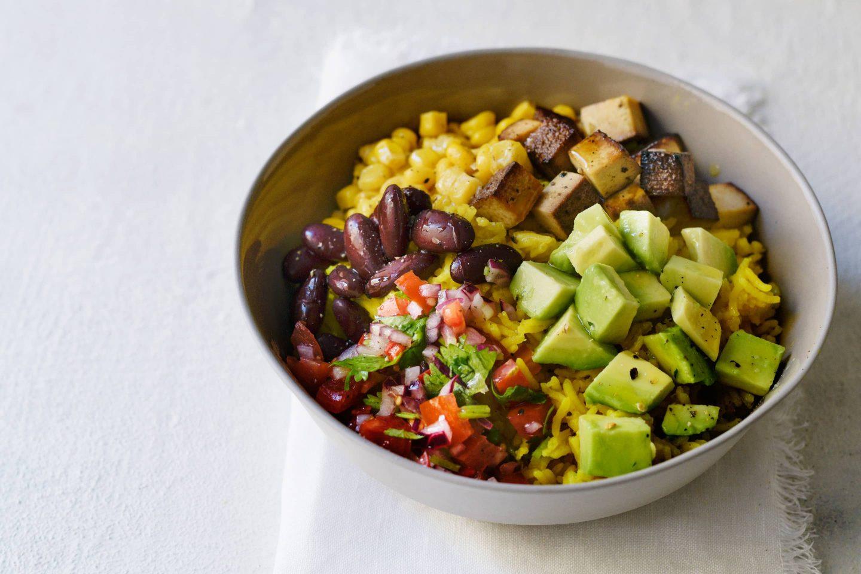 Vegane Burrito Bowl Tofu, Avocado-Würfeln und Tomatensalsa in einer Schale