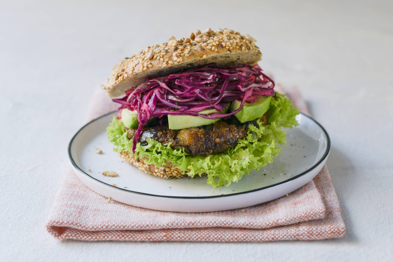 Thymian-Melanzani-Burger mit Rotkraut und Avocado auf einem hellen Teller mit rosafarbener Stoffserviette
